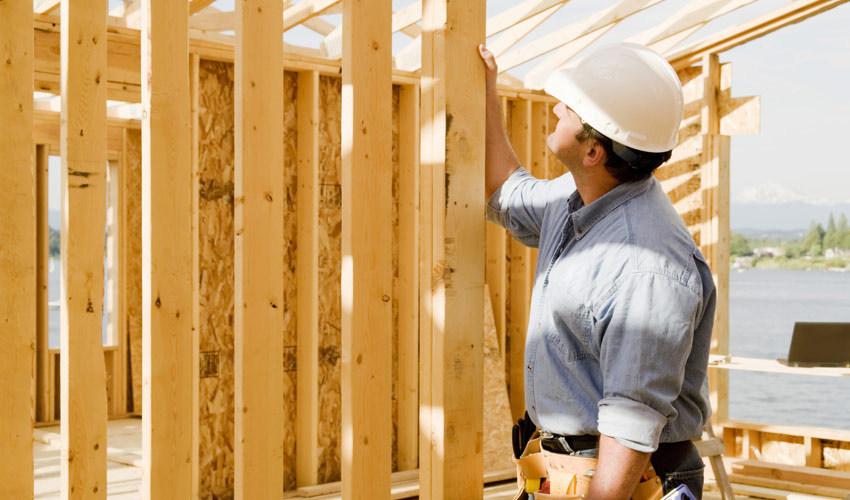 construction worker examining a newly framed wall