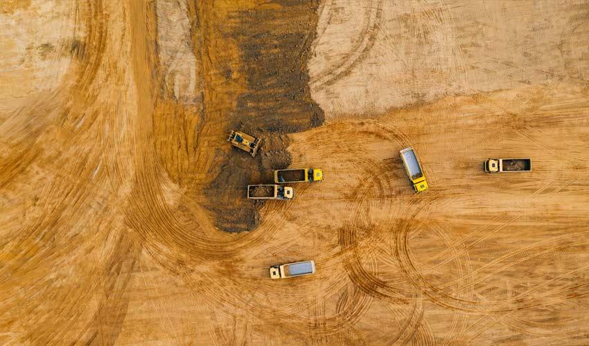 trucks on plot of land beginning new construction
