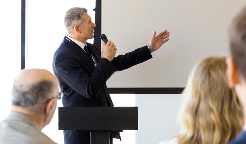 man standing at podium giving a presentation