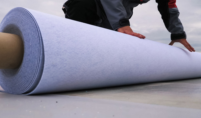 close-up of waterproofing material being rolled out